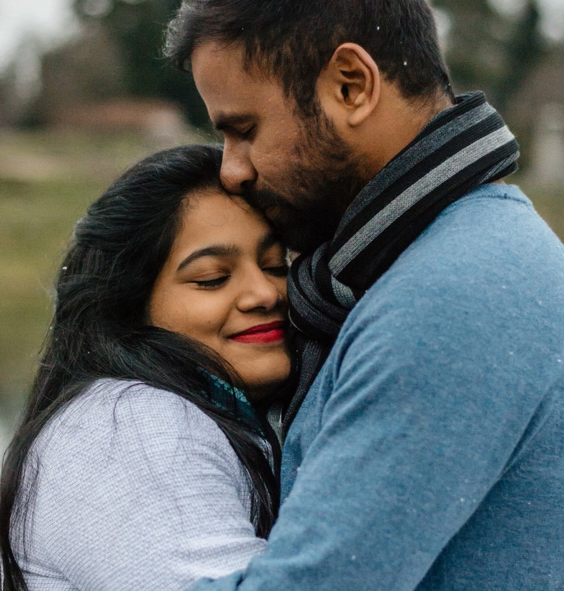 a man and woman hugging one another and smiling
