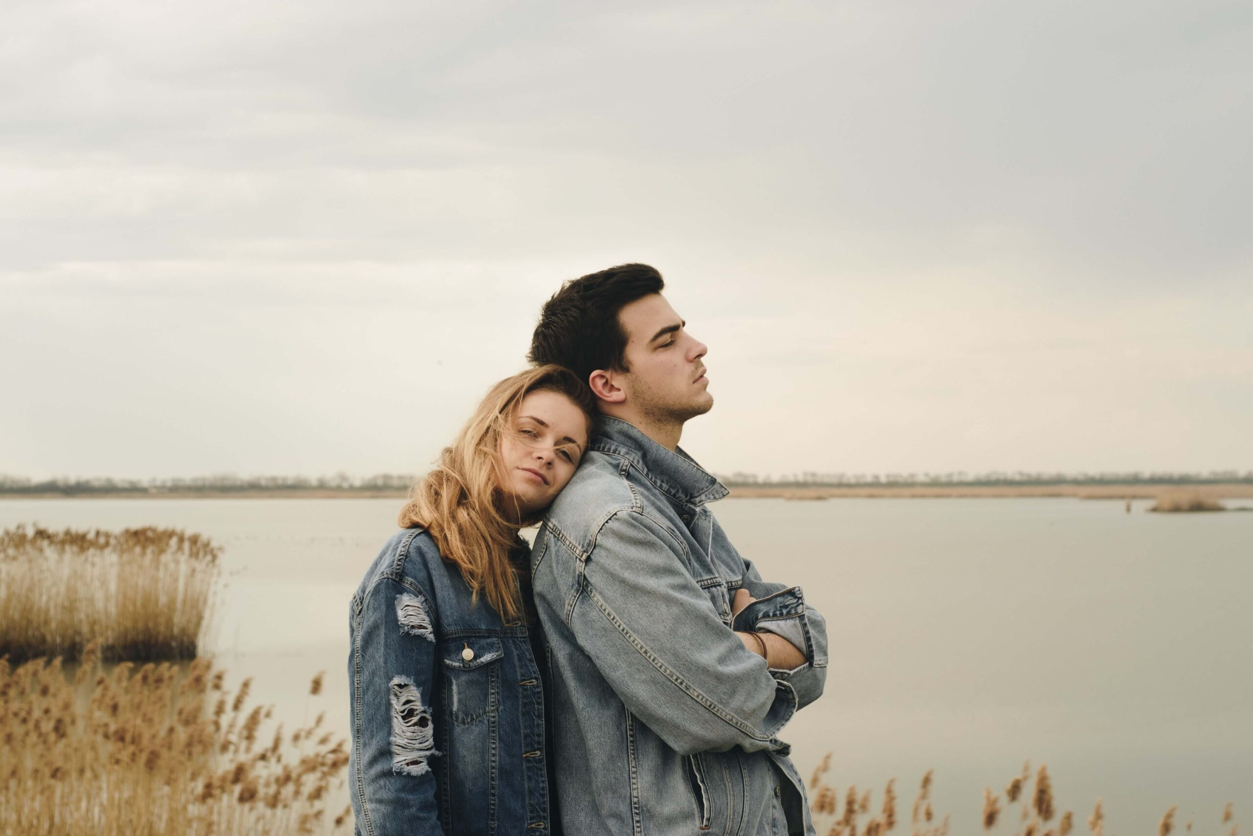 A somber-looking couple stands together at the bay
