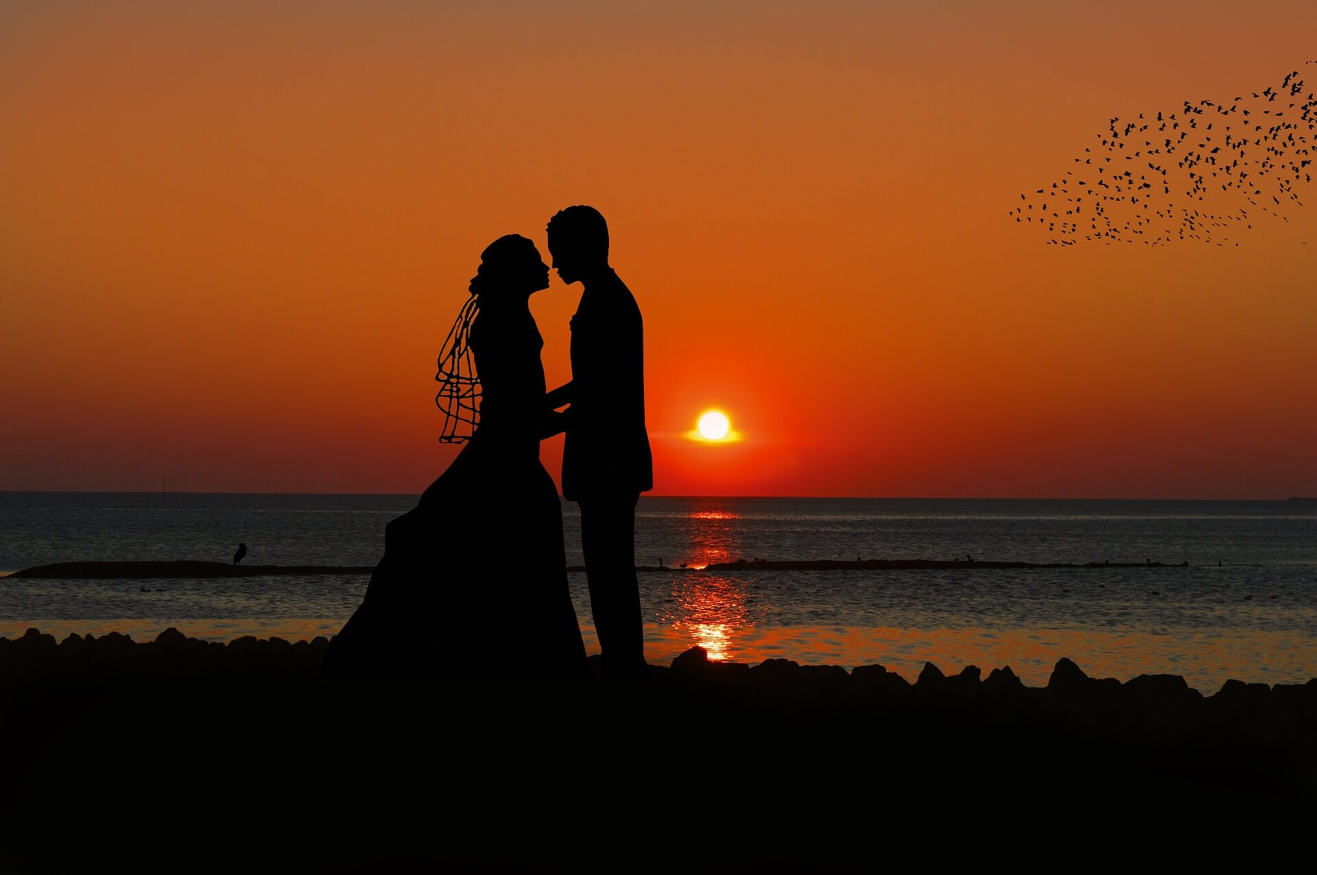 A silhouette of a bride and groom holding hands at sunset