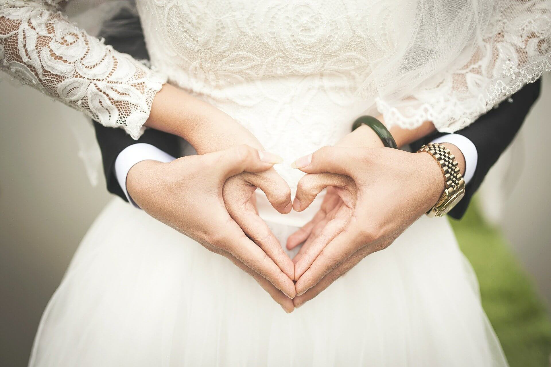 A man and woman at a wedding with hands held in a heart shape