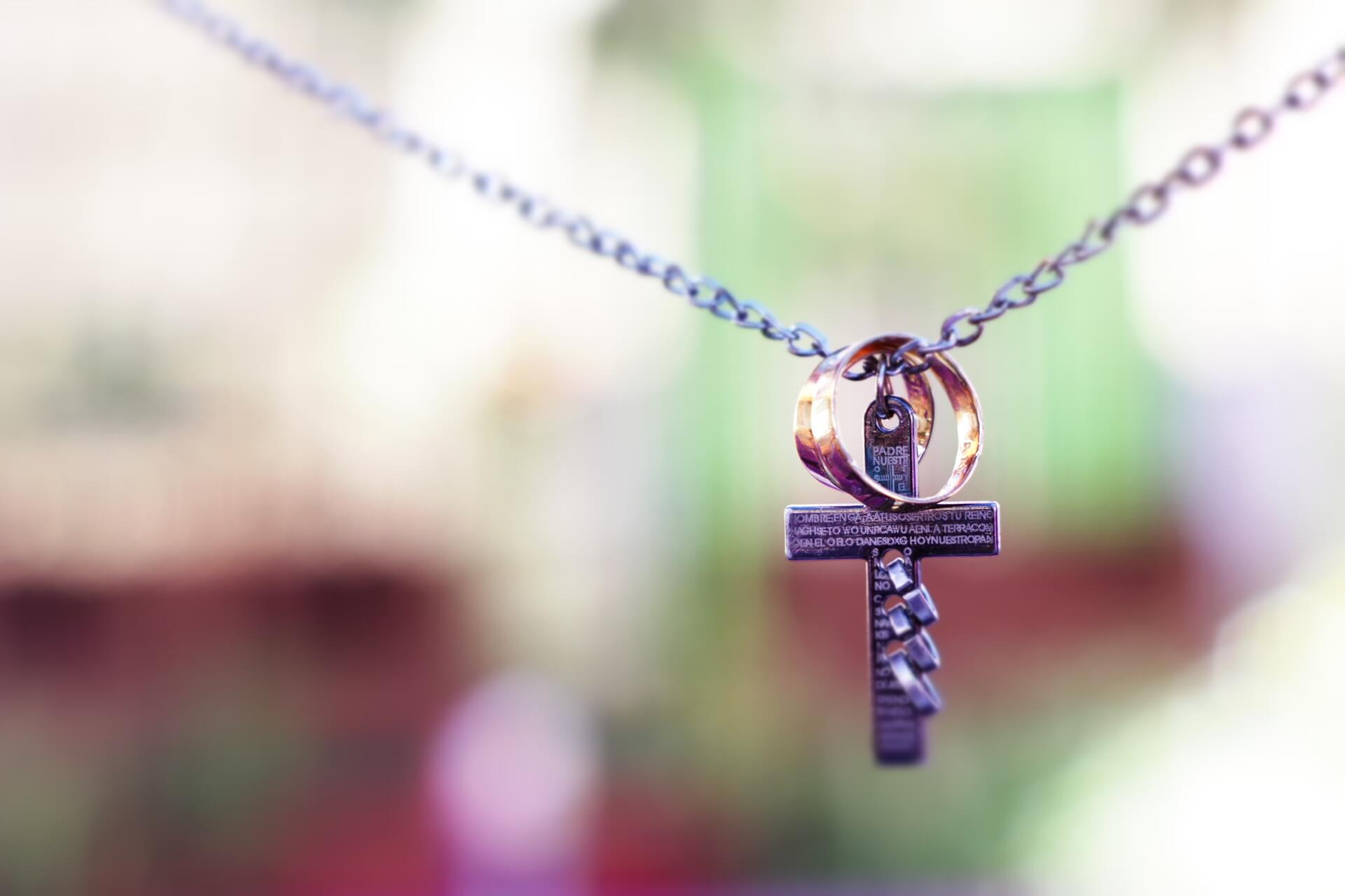 A necklace holding a cross and wedding bands