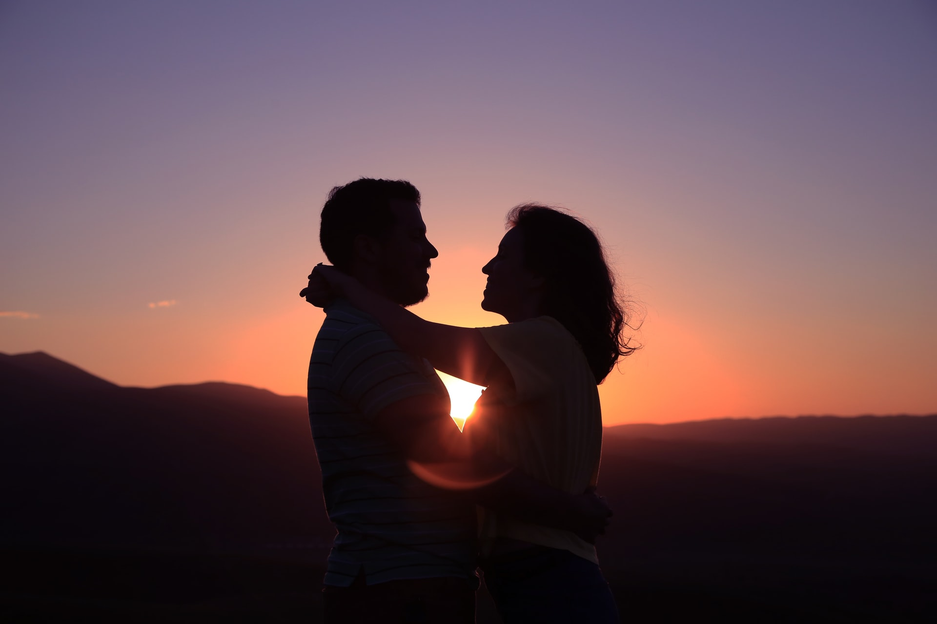 A couple embraces at sunset