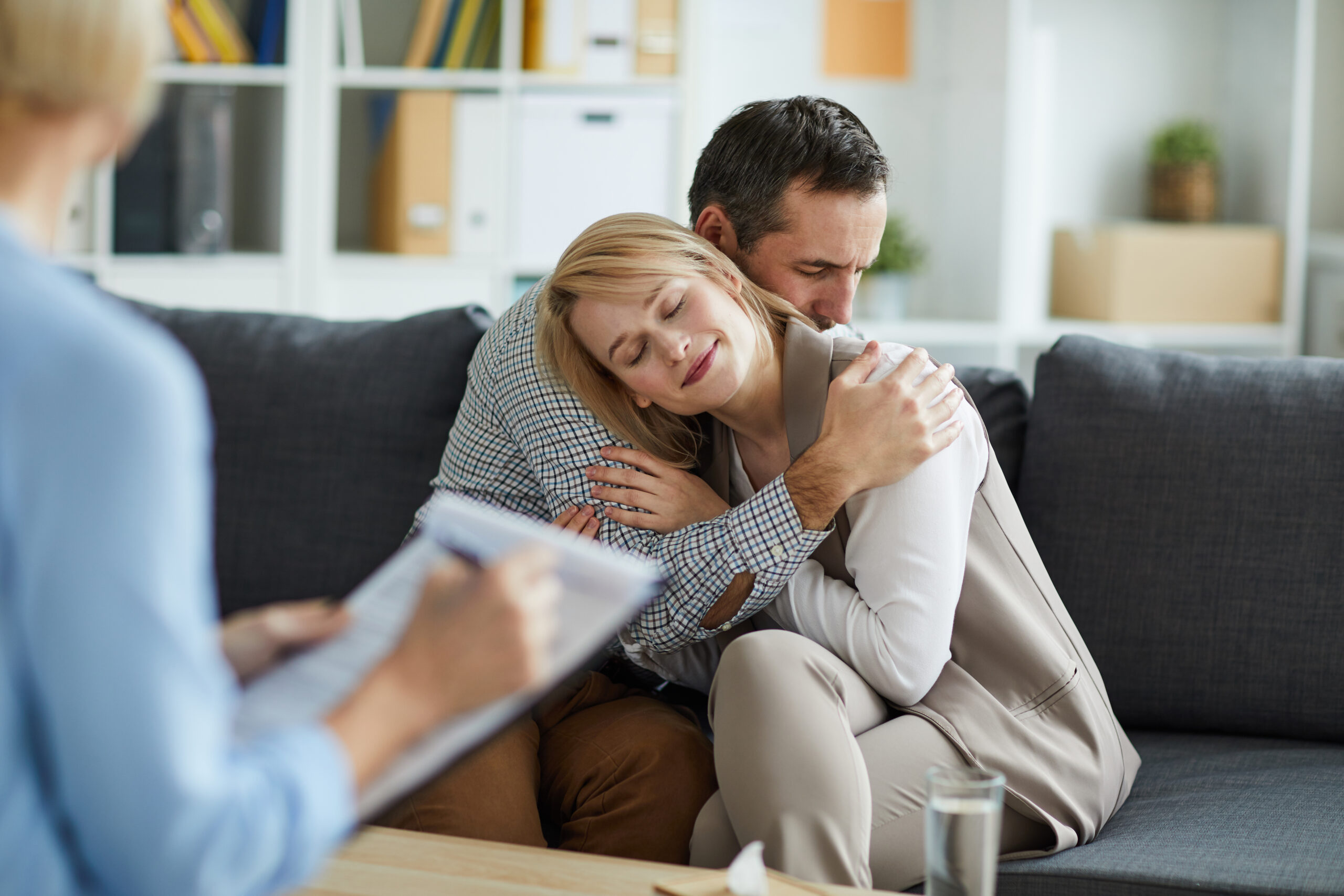 Young couple sitting on couch in embrace after consulting with counselor and solving their problem