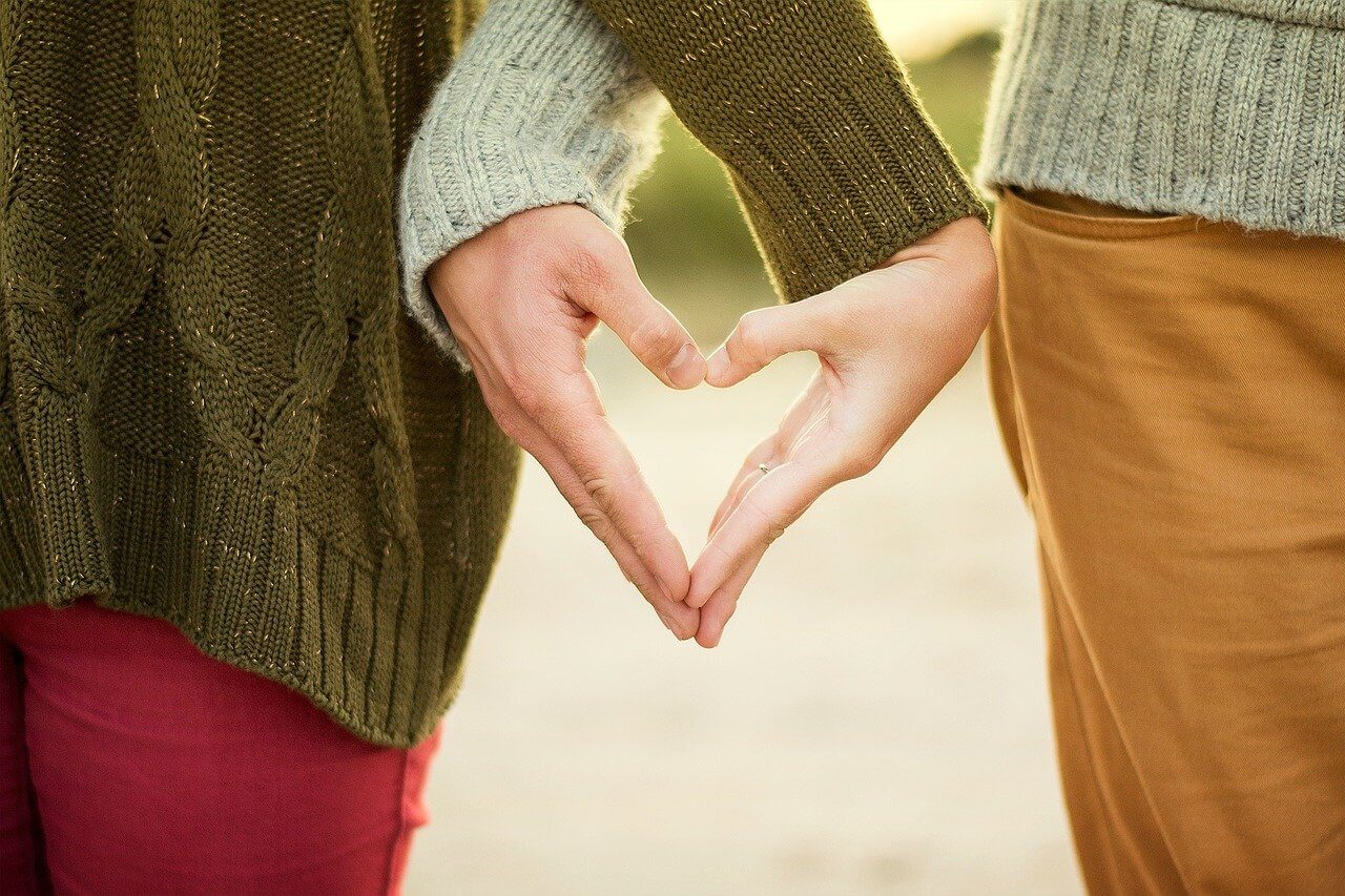 A couple with hands together forming a heart