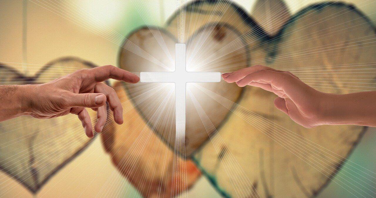 Hands touching a cross